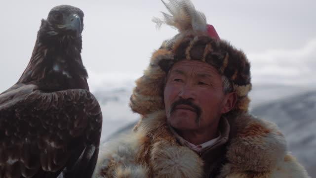 eagle hunter posing with golden eagle - altai mountains, mongolia - mongoliet bildbanksvideor och videomaterial från bakom kulisserna