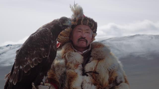 Eagle Hunter posing with Golden Eagle - Altai Mountains, Mongolia