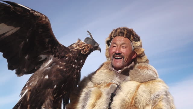eagle hunter posing with golden eagle - altai mountains, mongolia - mantel stock-videos und b-roll-filmmaterial