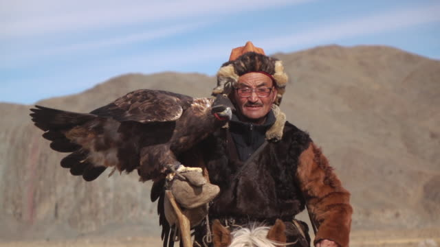 stockvideo's en b-roll-footage met eagle hunter posing with golden eagle - altai mountains, mongolia - oost aziatische cultuur