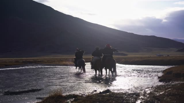 eagle hunters near the river in mongolia - golden eagle stock videos & royalty-free footage