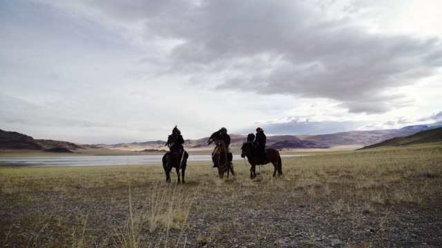 eagle hunters near the river in mongolia - independent mongolia stock videos & royalty-free footage