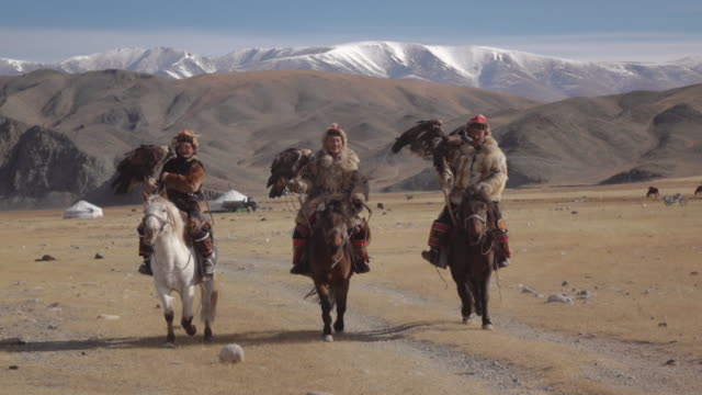 eagle hunters riding horses with golden eagles - altai mountains, mongolia - drei personen stock-videos und b-roll-filmmaterial