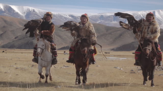 eagle hunters riding horses with golden eagles - altai mountains, mongolia - indigenes volk stock-videos und b-roll-filmmaterial