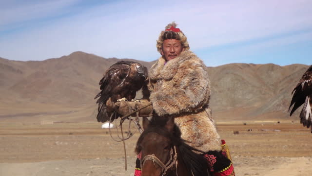 stockvideo's en b-roll-footage met eagle hunters riding horses with golden eagles - altai mountains, mongolia - mongolië