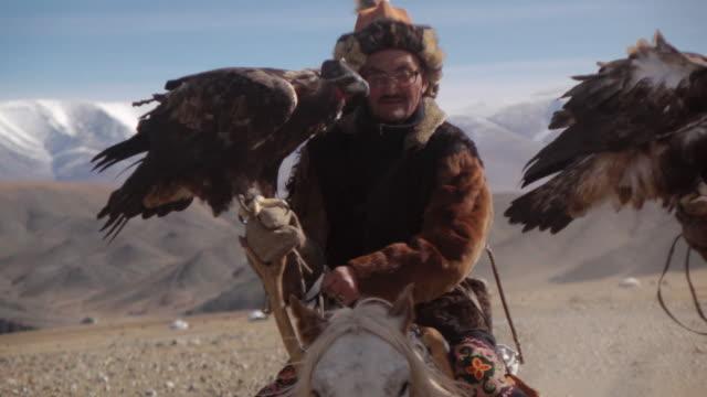 vídeos de stock, filmes e b-roll de eagle hunters riding horses with golden eagles - altai mountains, mongolia - animal de trabalho