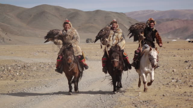 Eagle Hunters riding horses with Golden Eagles - Altai Mountains, Mongolia