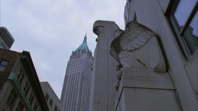 la ms eagle statue on city bank-farmers trust company building at 20 exchange place with trump building at 40 wall street in background / manhattan, new york, new york, usa - アールデコ点の映像素材/bロール