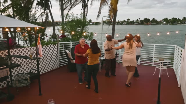 eal time video of mature and senior friends dancing at dusk on florida balcony - small group of people stock videos & royalty-free footage
