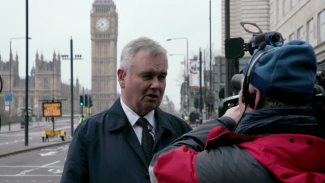 stockvideo's en b-roll-footage met eamonn holmes waits to do a live broadcast westminster bridge the morning after terror attack westminster london - eamonn holmes