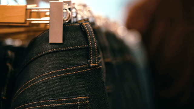 eans hanging on hangers on the rack in the clothing store. - jeans stock videos & royalty-free footage