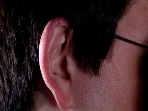 ear of young man with black hair who removes glasses smoothes hair behind ear and finally waggles ear - ear stock videos & royalty-free footage