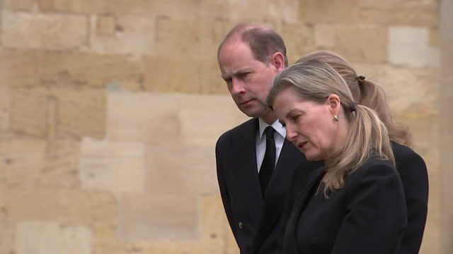 """earl and countess of wessex and daughter lady louise windsor looking at tributes outside st george's chapel for prince philip, duke of edinburgh - """"bbc news"""" stock-videos und b-roll-filmmaterial"""