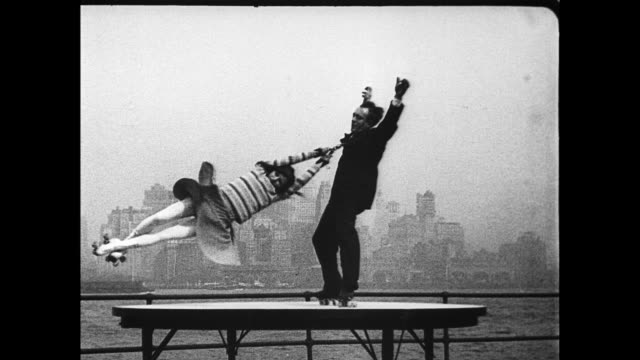 Earl Van Horn and Inez Van Horn roller skating on roofttop platform with the New York city skyline in background / skaters spin around in circles /...