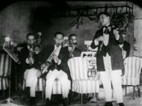 stockvideo's en b-roll-footage met b/w early 1920s musicians wearing jackets in band playing in nightclub / nyc / newsreel - saxofonist
