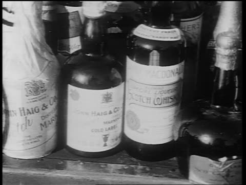 b/w early 1930s close up pan bottles of liquor on small table - einige gegenstände mittelgroße ansammlung stock-videos und b-roll-filmmaterial
