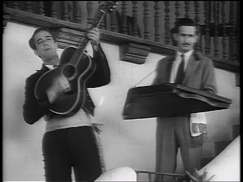 vídeos de stock e filmes b-roll de b/w early 1930s mexican musicians playing on stairway + singing / california / newsreel - monocromo