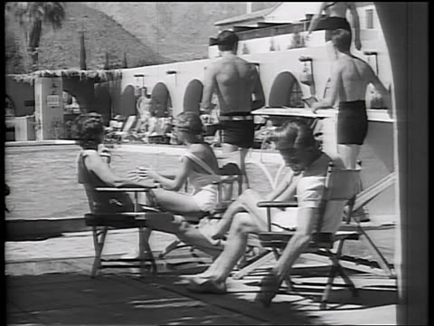 b/w early 1930s people sitting by swimming pool at resort / california / newsreel - newsreel stock videos and b-roll footage