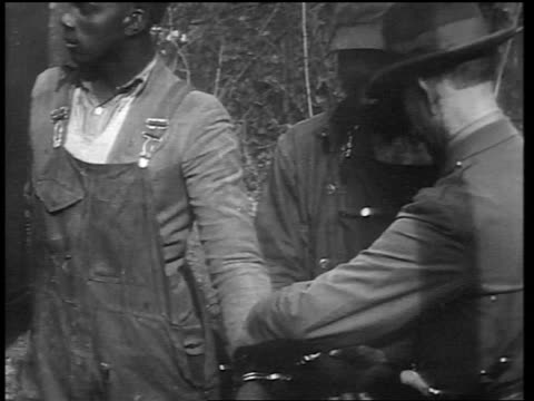 B/W early 1930s police officer handcuffing 2 Black men together in forest