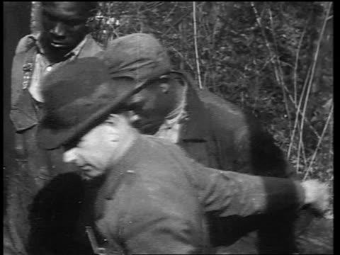 b/w early 1930s police officer leading 2 handcuffed black men away - 密輸点の映像素材/bロール