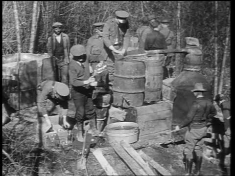 b/w early 1930s police other men examining outdoor distillery in forest - 密輸点の映像素材/bロール