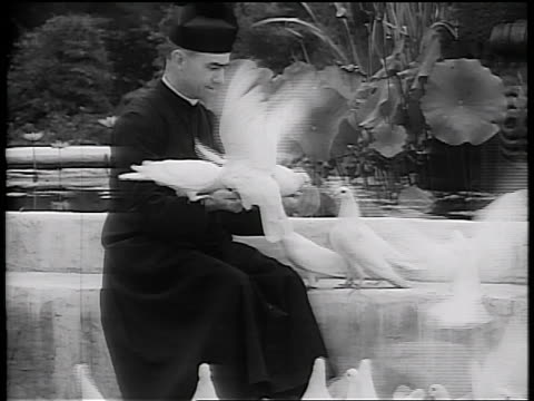 vidéos et rushes de b/w early 1930s priest sitting by fountain playing with white doves / california / newsreel - prêtre