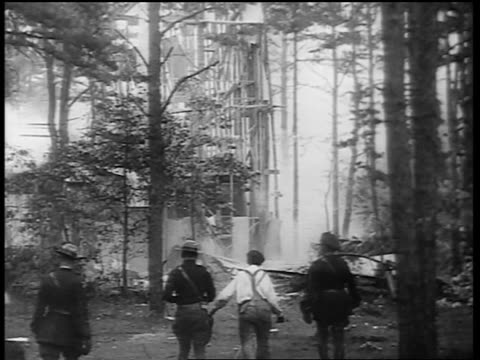 b/w early 1930s rear view police other men walking to smoking rubble of exploded building - 禁酒法点の映像素材/bロール