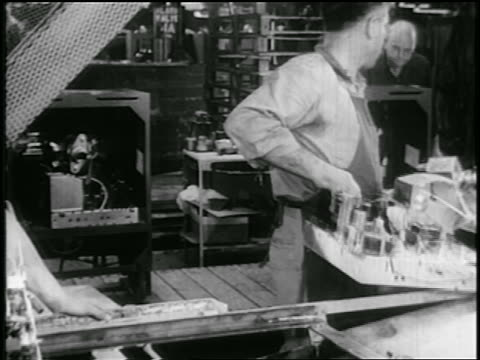 b/w early 1950s man carrying television parts to cabinets moving on assembly line in rca factory - interconnect plug stock videos & royalty-free footage