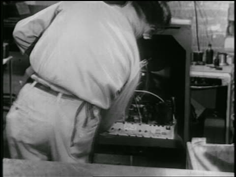 b/w early 1950s rear view man installing electronics in cabinet on assembly line in rca factory - interconnect plug stock videos & royalty-free footage