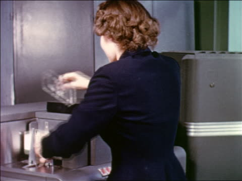 early 1950s woman placing stack of punch cards onto reader of large computer - punch card stock videos & royalty-free footage