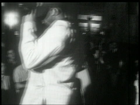 B/W early 1960s Black man on stage singing to audience of young white men
