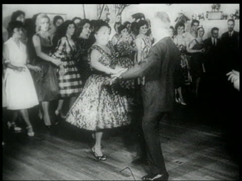 b/w early 1960s crowd around middle aged couple doing the twist on dance floor - early rock & roll stock videos & royalty-free footage
