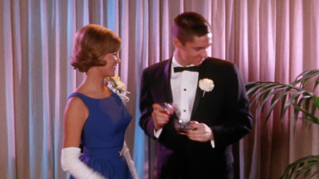 vidéos et rushes de early 1960s medium shot teen couple in formalwear drinking a toast and dancing in front of curtain - couple d'adolescents