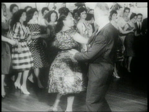 B/W early 1960s middle aged couple doing the Twist at dance / crowd in background