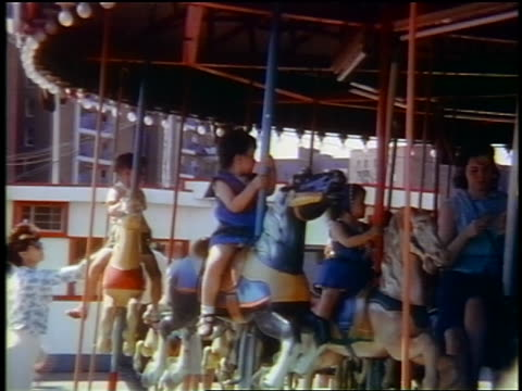 early 1960s people on carousel / woman waving / amusement park in queens, ny / jump cuts - fairground stock videos and b-roll footage