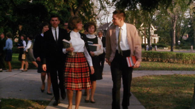 Early 1960s tracking shot pan high school students in walking to school, talking and carrying books