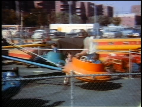 early 1960s woman helping two small girls get onto amusement ride / queens, ny / home movie - fairground stock videos and b-roll footage