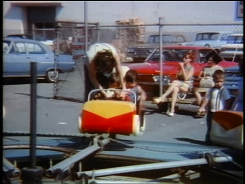 early 1960s woman helping two small girls into amusement ride / girls wave to camera / home movie - fairground stock videos and b-roll footage