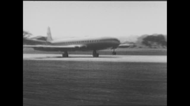early airplane takes off / pilot in cockpit of plane with men helping him roll up sleeve of his flight suit / rear shot pilot waves as plane moves... - human age stock videos & royalty-free footage