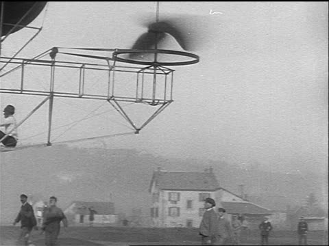 b/w 1925 pan early airship hovering above ground + landing with men running underneath - 1925 stock videos & royalty-free footage