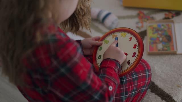 vídeos de stock, filmes e b-roll de desenvolvimento infantil. menina aprendendo tempo com relógio brinquedo em casa - conta artigo de armarinho