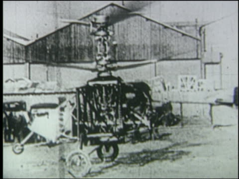 b/w 1936 early double-rotored helicopter hovering just above ground - hubschrauber stock-videos und b-roll-filmmaterial