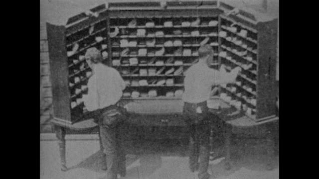 1967 early footage of postal workers placing small amounts of mail in slots - post structure stock videos & royalty-free footage