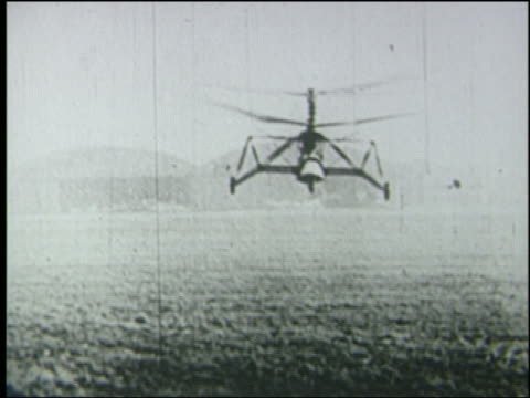 b/w 1936 pan early helicopter flies low toward + past camera - hubschrauber stock-videos und b-roll-filmmaterial