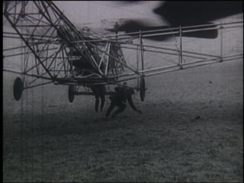 b/w early helicopter hovering above ground - hubschrauber stock-videos und b-roll-filmmaterial