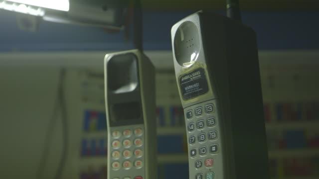 vídeos de stock e filmes b-roll de early mobile phones on a work desk at home, medium shot - telefone sem fio