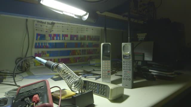early mobile phones on a work desk at home, wide shot - sladdlös telefon bildbanksvideor och videomaterial från bakom kulisserna