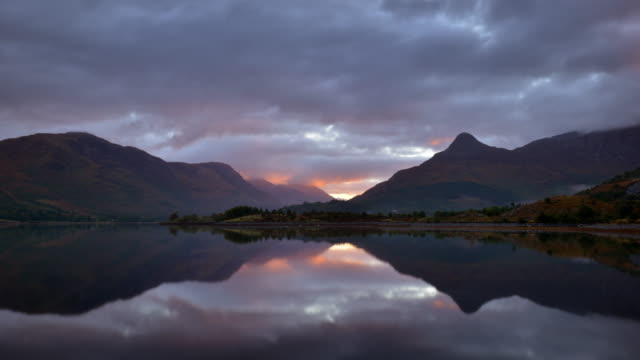 early moring sunsrise over loch leven and the pap of glencoe - schottisches hochland stock-videos und b-roll-filmmaterial