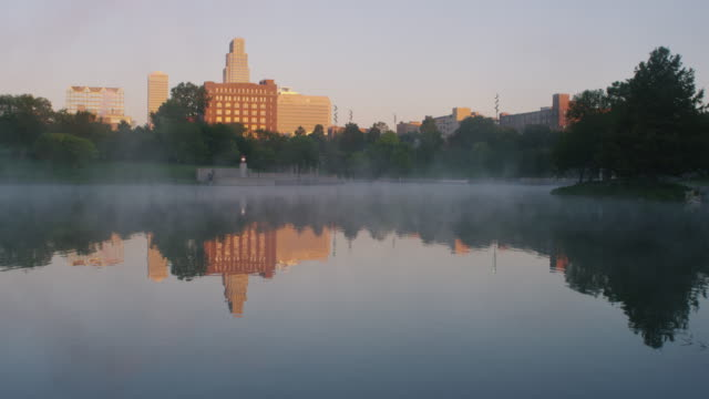 early morning at an urban park - steam rises from the pond - cityscape in background. - nebraska stock videos & royalty-free footage