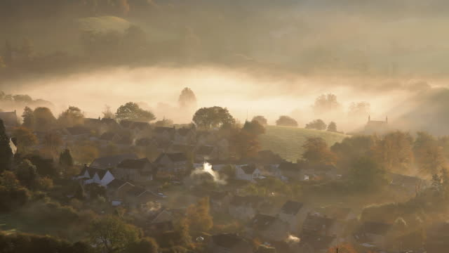 early morning autumn mist and chimney smoke from the village of uley, gloucestershire, uk - gloucestershire stock videos and b-roll footage